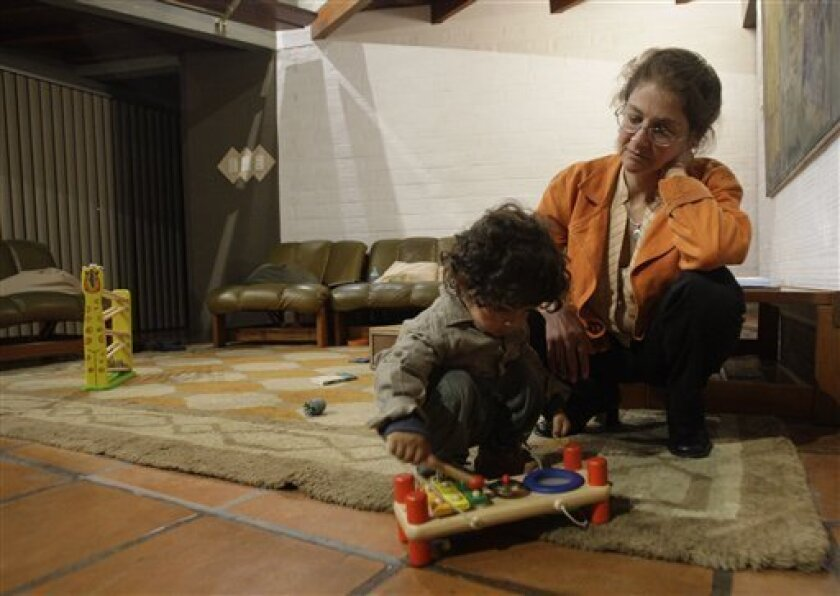 US political activist Lori Berenson watches her eighteen-month-old son Salvador Apari play in their home after an interview with The Associated Press in Lima, Peru, Tuesday Nov. 9, 2010. Berenson, 40, who served three-quarters of a 20-year sentence for collaborating with leftist rebels in Peru, walked free for the second time after a judge reinstated her parole initially ruled in May. (AP Photo/Karel Navarro)