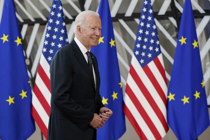 Biden, smiling, walks in front of U.S. and EU flags.