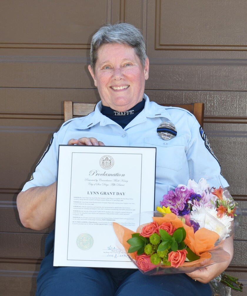 "SDPD RSVP traffic unit member Lynn Grant holding a proclamation declaring July 8 ""Lynn Grant Day"" in San Diego District Five."