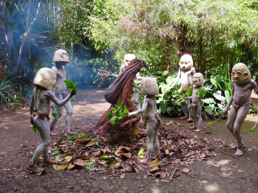 Members of the Warup clan in Pulga Village near Hagen. The men, covered in white clay and donning ceramic masks weighing about 20 pounds, dance around the matriarch to ward off evil spirits and neighboring warring clans.