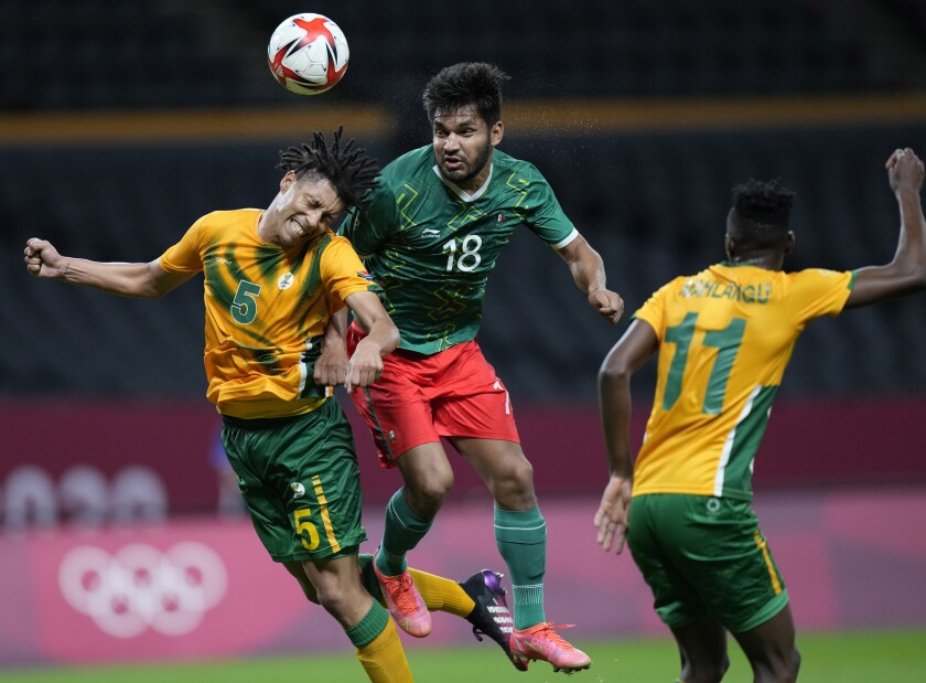 Luke Fleurs of South Africa and Mexico's Eduardo Aguirre go for a header during Mexico's 3-0 win.