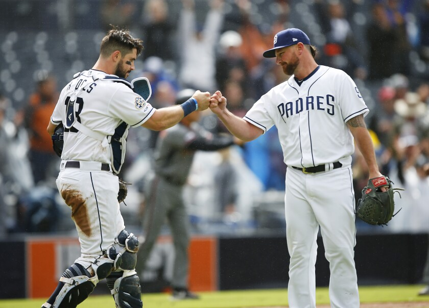 San Diego Padres catcher Austin Hedges and closer Kirby Yates celebrate after a 5-2 win over the Arizona Diamondbacks at Petco Park.