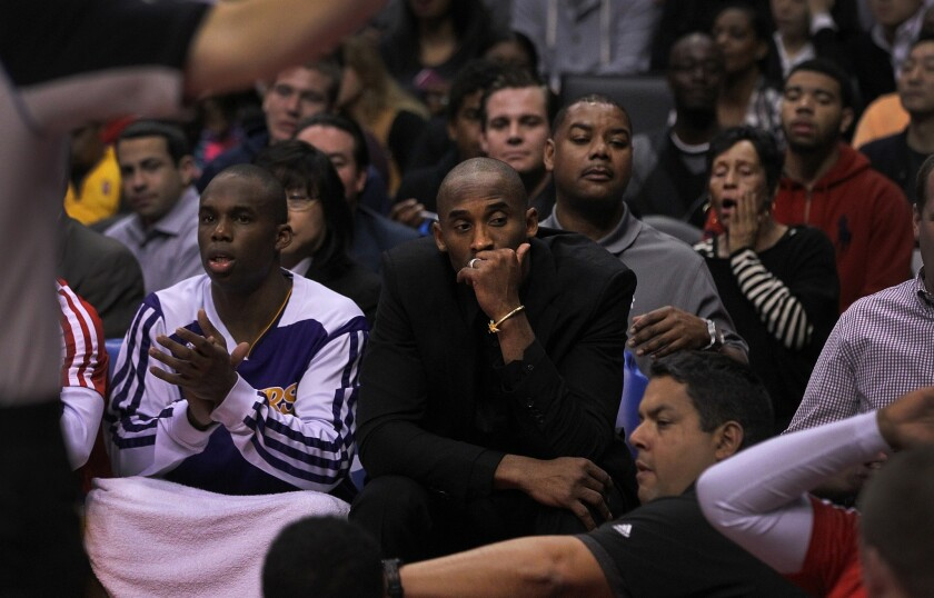 Injured Kobe Bryant looks away from the court during the Clippers' 123-87 rout of the Lakers last Friday at Staples Center.