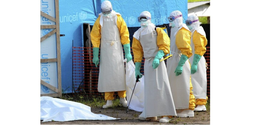 Health workers prepare to load the body of a woman who died of the Ebola virus into a pickup truck at an isolation site in Foya, Liberia.