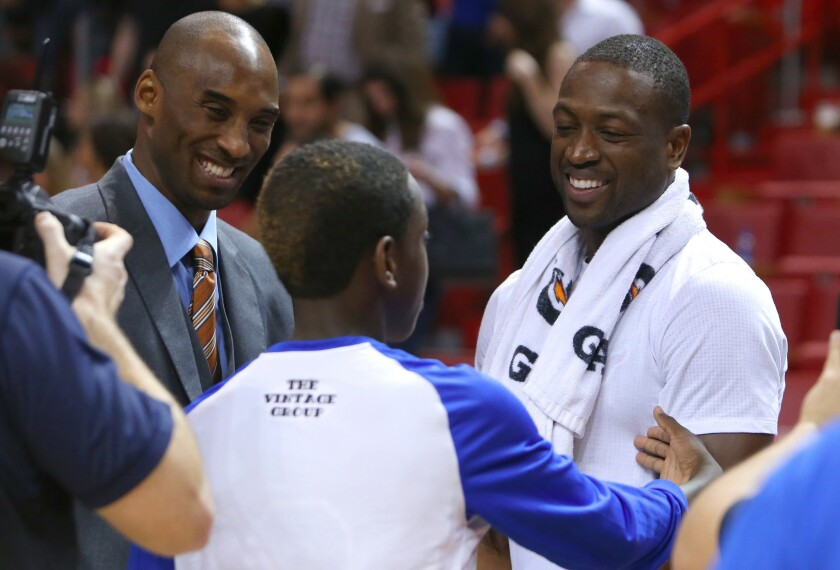 Kobe Bryant, left, talks with the Miami Heat's Dwyane Wade, right, after the Lakers' 101-88 loss in Miami on Nov. 10.