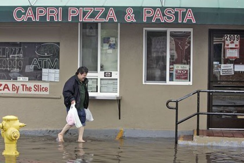 Imilio Valencia, co-owner of a Mission Beach taco shop, took off his shoes to carry supplies yesterday. (Laura Embry / Union-Tribune)