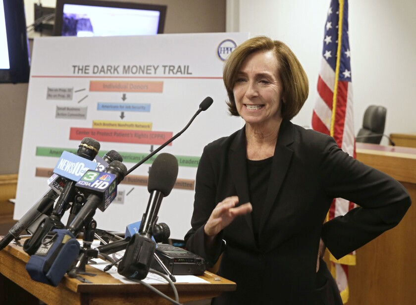 """Ann Ravel stands at a lectern. Behind her is a poster with the title """"The Dark Money Trail."""""""