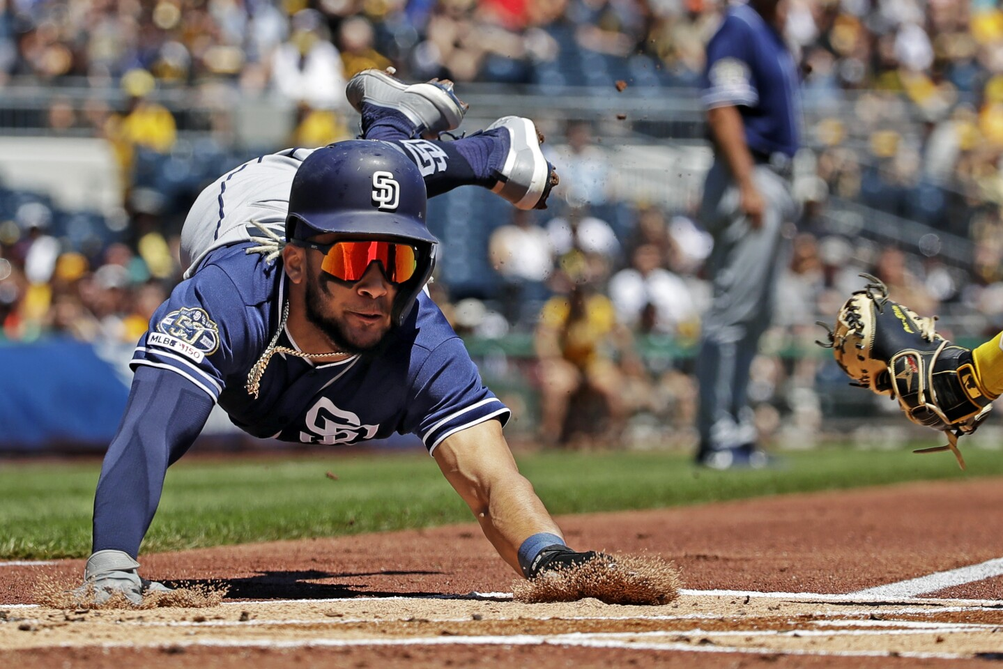 San Diego Padres' Fernando Tatis Jr., left, slides around the tag attempted by Pittsburgh Pirates catcher Elias Diaz, right rear, during the first inning of a baseball game in Pittsburgh, Sunday, June 23, 2019. Tatis tagged up at third on a sacrifice fly to second by Hunter Renfroe. (AP Photo/Gene J. Puskar)