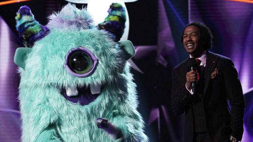 """Monster and host Nick Cannon in deep conversation during the premiere episode of Fox's reality competition """"The Masked Singer."""""""