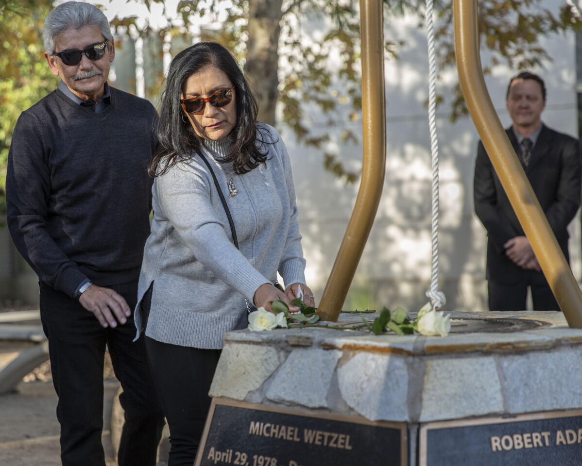 LOS ANGELES, December 2, 2019: Marie Velasco places a rose for her daughter, Yvette Velasco, at a memorial at Cal State San Bernardino on December 2, 2019. Yvette Velasco was one of the youngest victims at the mass shooting in San Bernardino four years ago which left 14 people dead and 22 others wounded. (Allison Zaucha / For The Times)