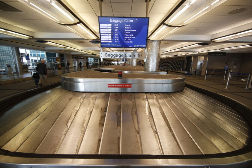 FILE - In this March 20, 2020 file photo, an empty baggage carousel spins in Denver International Airport as travelers deal with the spread of the coronavirus in Denver. Unions are gaining support in Congress for another $32 billion in federal aid to protect airline workers from layoffs for another six months. Still, it's too early to say how the issue will turn out. (AP Photo/David Zalubowski, File)