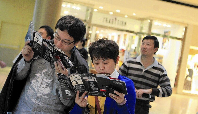Members of a Chinese tour group peruse shopping brochures at the Beverly Center.