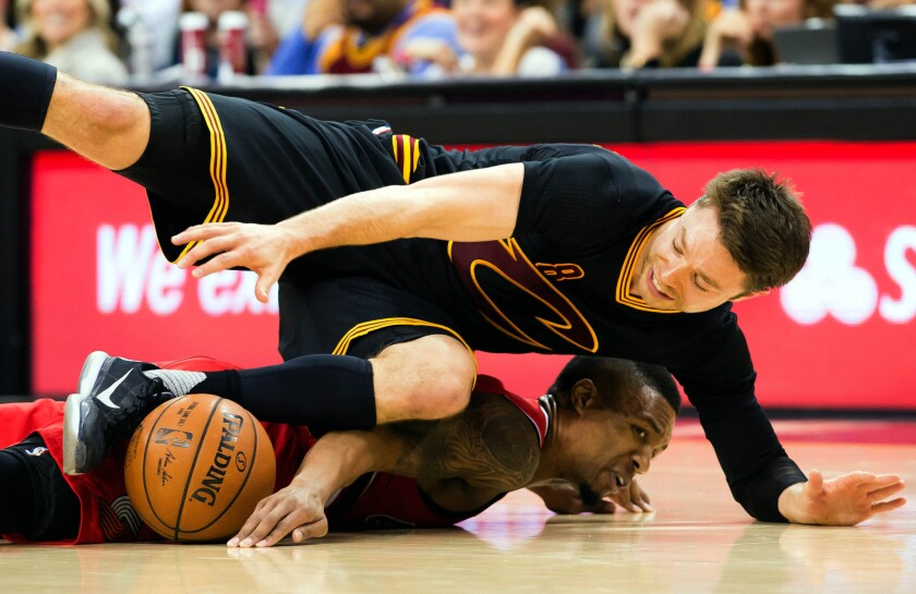 Cleveland guard Matthew Dellavedova lands on top of Trail Blazers guard Damian Lillard while battling for a loose ball during a game Dec. 8, 2015.