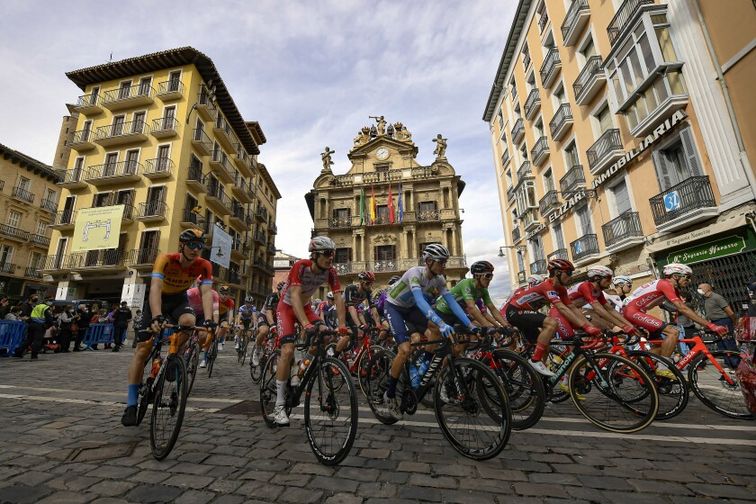 La Vuelta pack race cross in front of the City Hall at Plaza del Ayuntamiento square during the second stage of La Vuelta between Pamplona and Lekunberri, in Pamplona, northern Spain, Wednesday, Oct. 21, 2020. (AP Photo/Alvaro Barrientos)