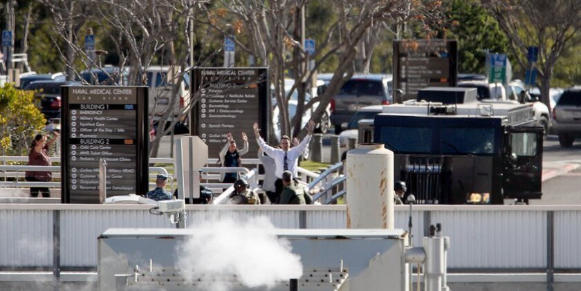 Navy Medical Center San Diego personnel come out of a building with their hands up after reports there was an active shooter at the site.