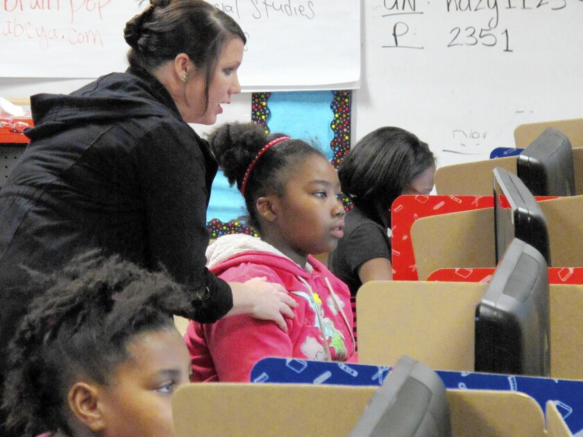 Teacher Angela Wathanacharoen helps fourth-grader Janae Dale with a writing and computer lesson at Frank Rushton Elementary School in Kansas City, Kan. The school joined others in suing the state over a lack of education funding.