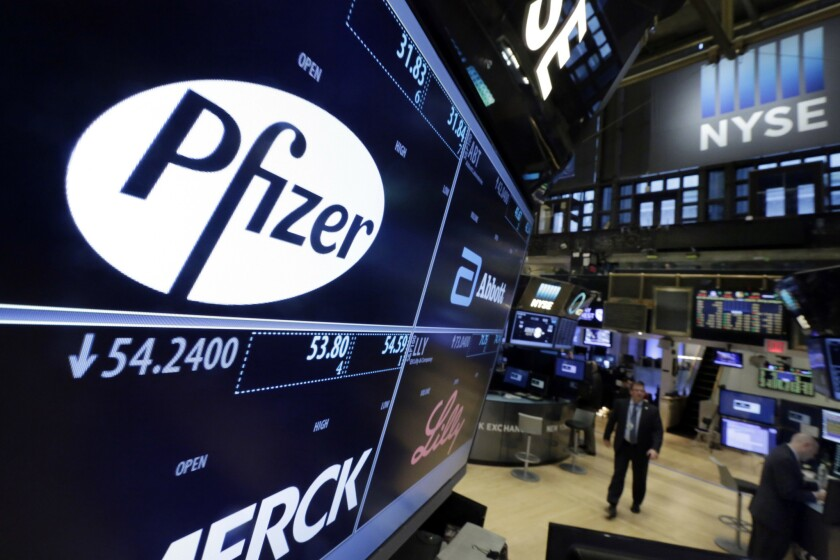 A monitor at the New York Stock Exchange shows the names and logos of Pfizer and other drugmakers.