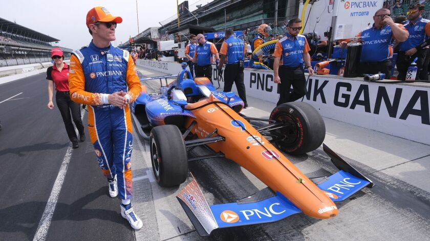 Scott Dixon, of New Zealand, walks around his car before the start of the final practice session for