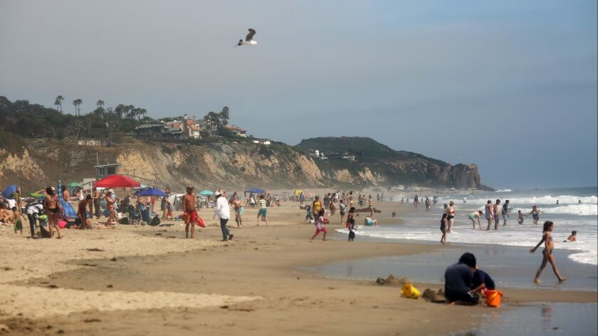 Crowds gather at Zuma Beach in Malibu on a warm day in June. A report released by Heal the Bay on Thursday gave the beach a failing grade in water quality.