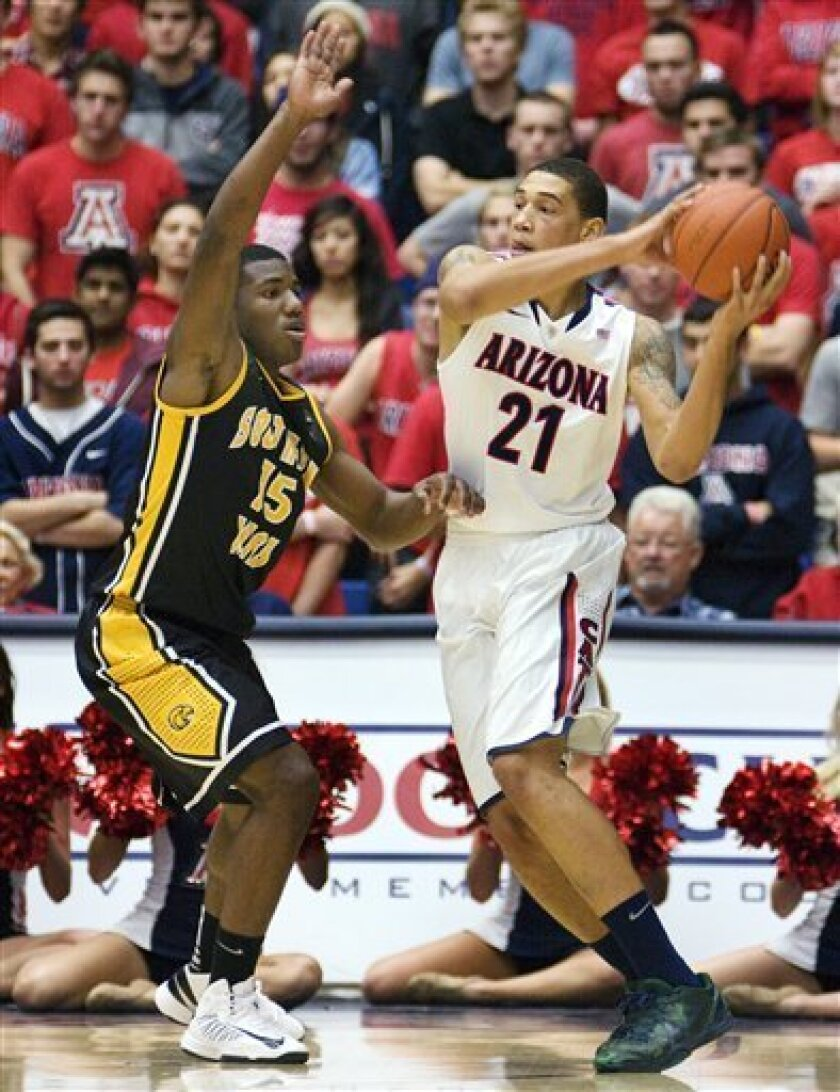 Arizona's Brandon Ashley (21) looks to pass the ball around Southern Mississippi's Deon Edwin (15) during the first half of an NCAA college basketball game at McKale Center in Tucson, Ariz., Tuesday, Dec. 4, 2012. (AP Photo/Wily Low)