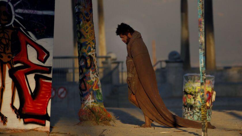 A homeless man walks around Venice Beach wearing a blanket November 6, 2017.