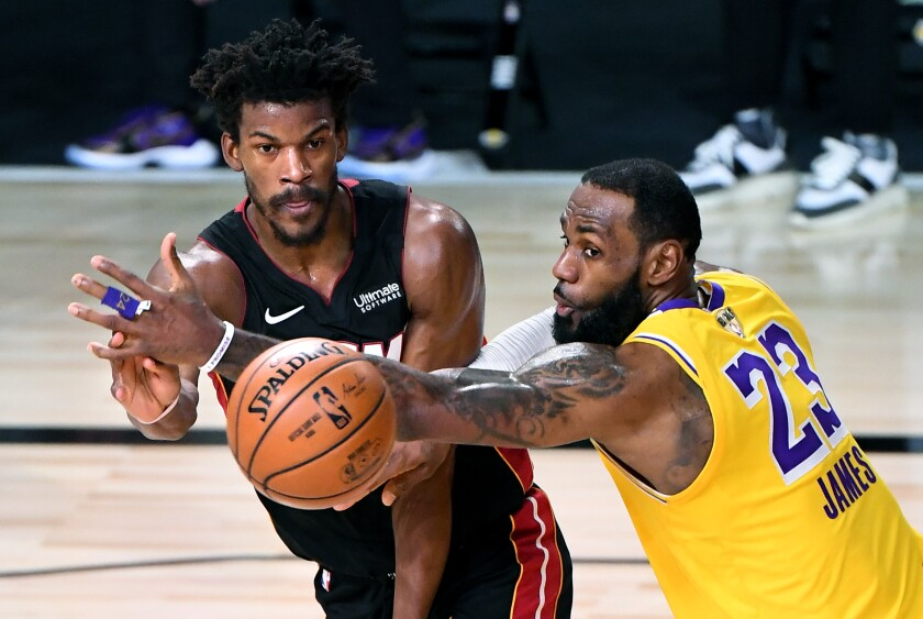 Lakers forward LeBron James tries to break up a pass from Miami Heat forward Jimmy Butler during the fourth quarter.