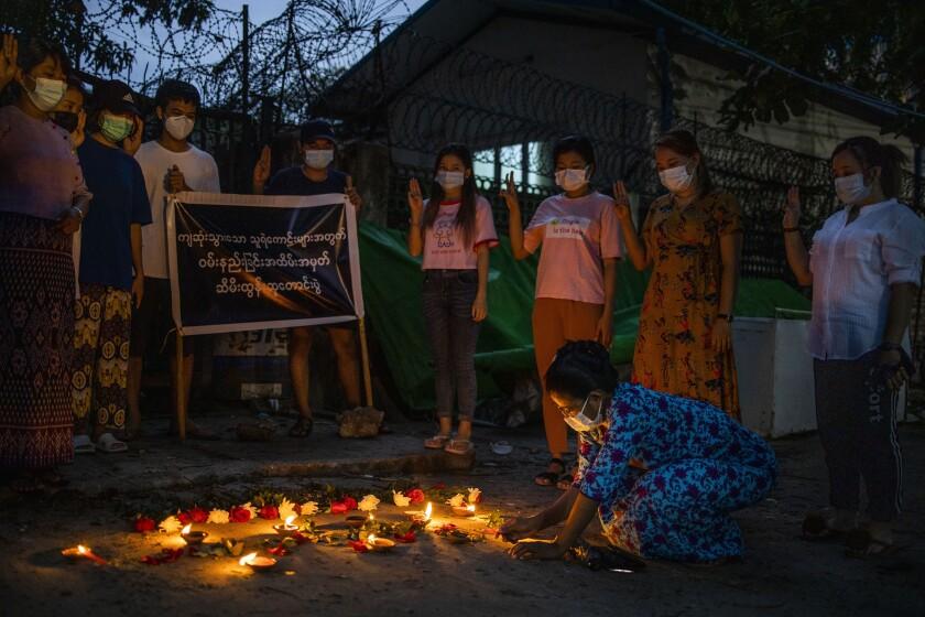Una mujer enciende una vela mientras otros hacen un saludo con tres dedos de una mano en alto, símbolo de la resistencia, durante una vigilia con velas en memoria de los fallecidos en la violenta respuesta de la junta militar a las protestas contra el golpe de Estado, en Yangón, Myanmar, el 16 de abril de 2021. (AP Foto)