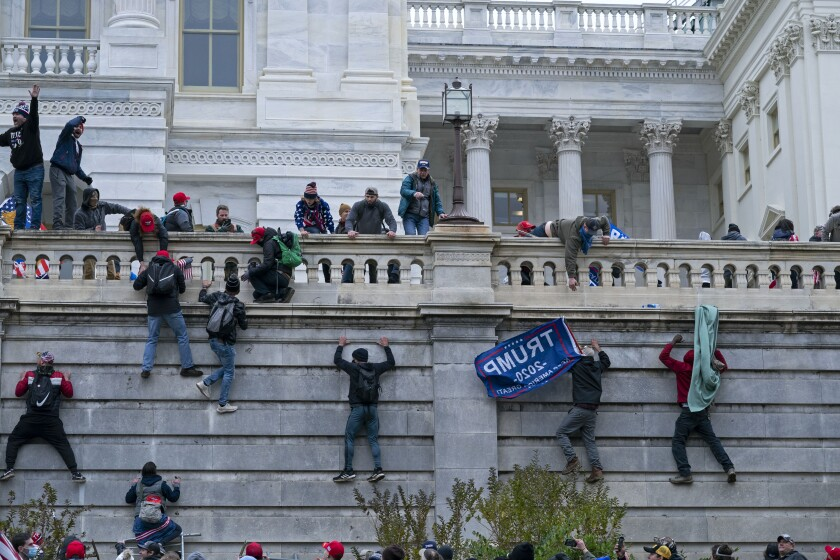 """FILE - In this Jan. 6, 2021 file photo, rioters climb the west wall of the the U.S. Capitol in Washington. First, some blamed the deadly Jan. 6 attack on the Capitol on left-wing Antifa antagonists, a theory quickly debunked. Then came comparisons of the rioters as peaceful protesters, or even """"tourists."""" Now, Trump allies rallying in support of those people charged in the Capitol riot are calling them """"political prisoners,"""" a stunning effort to revise the narrative of that deadly day. (AP Photo/Jose Luis Magana, File)"""