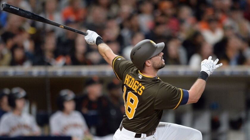 Padres catcher Austin Hedges (18) hits an RBI sacrifice fly during the fifth inning against the San Francisco Giants at Petco Park.