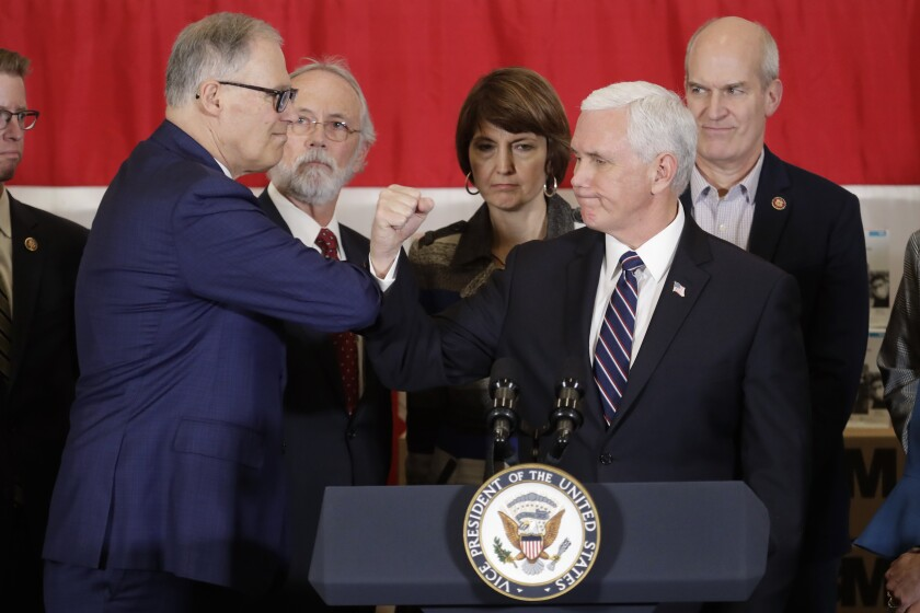 Vice President Mike Pence bumps elbows with Washington Gov. Jay Inslee, left, during a news conference, Thursday, March 5, 2020, at Camp Murray in Washington state. Pence was in Washington to discuss the state's efforts to fight the spread of the COVID-19 coronavirus, and officials have been avoiding shaking hands to prevent the spread of germs. (AP Photo/Ted S. Warren)