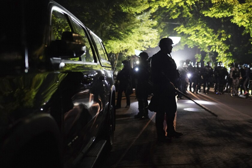 Portland police walk a neighborhood after dispersing protesters from the county Sheriff's Office early Saturday.