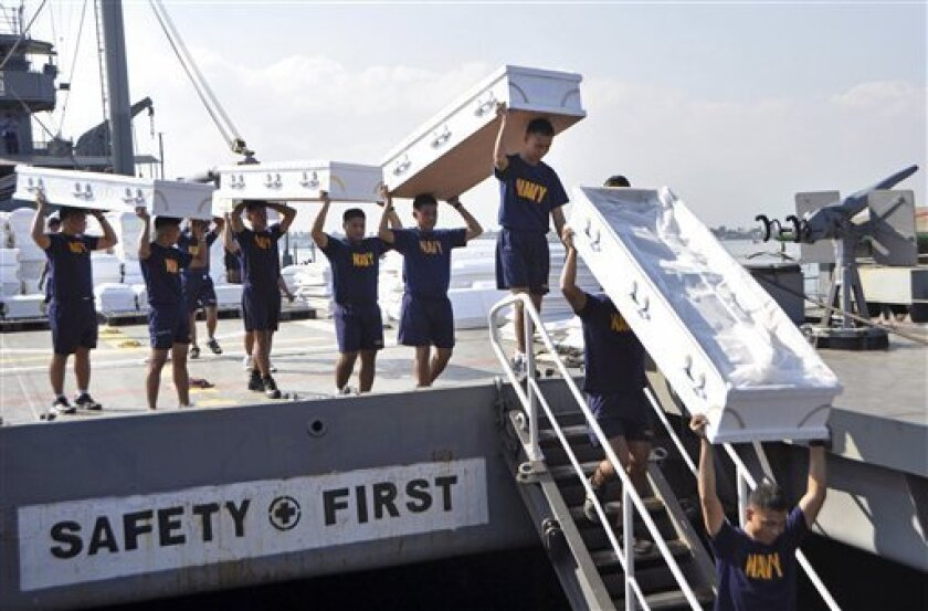 In this photo released by the Philippine Navy, navy personnel carry donated coffins on Philippine Navy ship BRP Laguna (LT-501) at the Sangley Point Naval Base, Cavite province, southern Philippines on Tuesday, Dec. 11, 2012 as it prepares to go to typhoon-affected areas of the country. Typhoon Bopha hit the main southern island of Mindanao last Tuesday, killing hundreds of people, mostly from flash floods that wiped away precarious communities in the southern region unaccustomed to typhoons. (AP Photo/Philippine Navy, SN2 Michael D. Namit) NO SALES