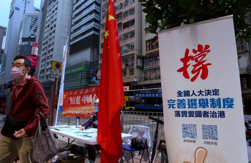 """A man walks past a banner that reads """"Support the proposal of National People's Congress (NPC) for the draft changes of election rules for Hong Kong"""" at a downtown street in Hong Kong Thursday, March 11, 2021. China's ceremonial parliament on Thursday approved a resolution to alter Hong Kong's election law that many see as effectively ending the city's already highly attenuated local democracy. (AP Photo/Vincent Yu)"""