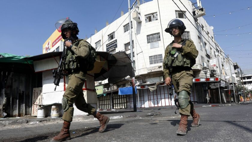 Israeli army soldiers take position during clashes with Palestinian stone throwers in the West Bank city of Hebron on August 3.