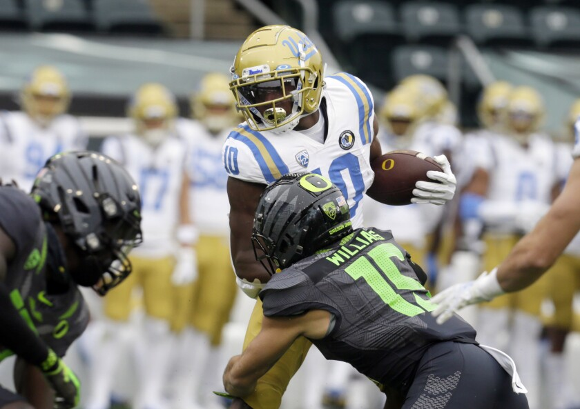 UCLA's Demetric Felton Jr. is tackled by Oregon's Bennett Williams during the first quarter.