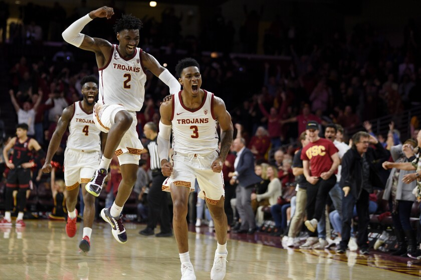 USC guard Elijah Weaver (3) celebrates with teammate Jonah Mathews (2) after making a three-point shot against Stanford on Jan. 18.