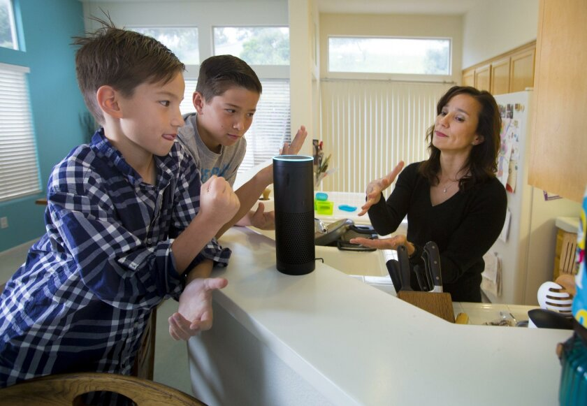 "Eight-year-old Sutton Philips, left, his brother, 10-year-old Greyson Philips, center, and their mom, Liz Philips, right, play a game of rock-paper-scissors with ""Alexa,"" their Amazon Echo wireless speaker and voice command personal assistant at their Scripps Ranch home."