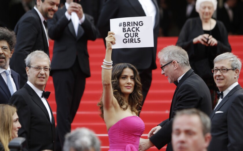 """Actress Salma Hayek holds up a sign reading """"#Bring back our girls"""" as she arrives for the screening of """"Saint-Laurent"""" at the Cannes film festival."""