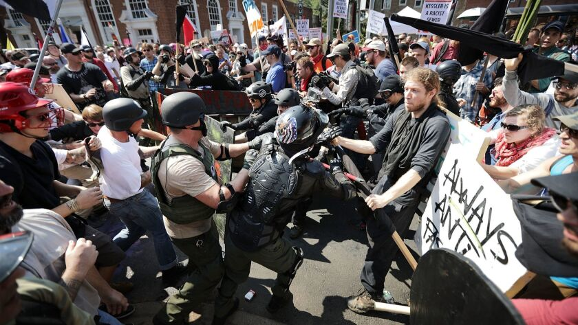 Neo-Nazis, white nationalists and members of the alt-right, at left, clash with counterprotesters last year in Charlottesville, Va.