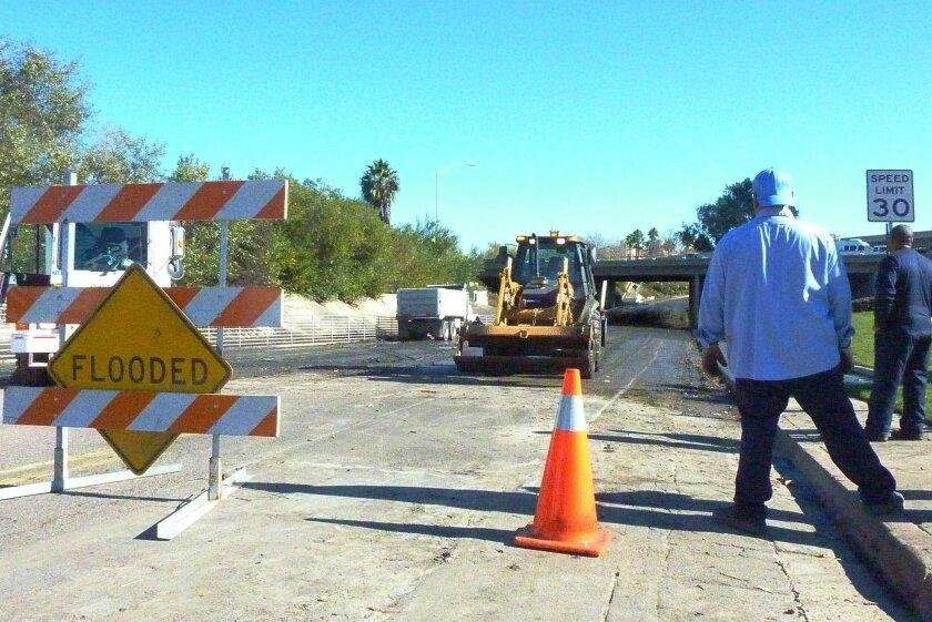 A work crew scrapes mud off of Camino de la Reina near Fashion Valley last week.