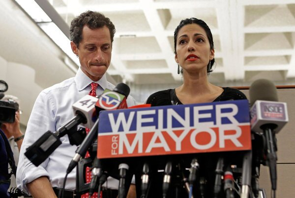 New York mayoral candidate Anthony Weiner, left, listens as his wife, Huma Abedin, speaks during a news conference at the Gay Men's Health Crisis headquarters in New York. The former congressman says he's not dropping out of the mayoral race in light of newly revealed sexting with a 22-year-old woman.