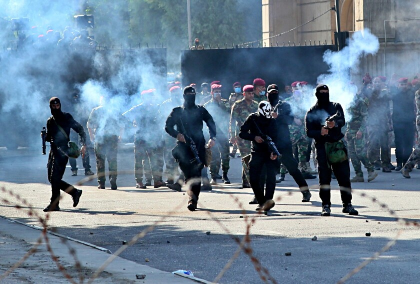 Iraqi security forces fire tear gas to disperse anti-government protesters Oct. 25 in central Baghdad.