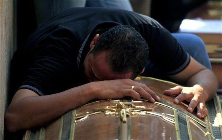An Egyptian relative of one of the Copts who were killed during clashes with the Egyptian army late Sunday, mourns over his coffin outside the morgue of the Copts hospital in Cairo, Egypt, Monday, Oct. 10, 2011. Egypt's Coptic church blasted authorities Monday for allowing repeated attacks on Christians with impunity as the death toll from a night of rioting rose to more than two dozen, most of them Christians who were trying to stage a peaceful protest in Cairo over an attack on a church. (AP Photo / Khalil Hamra)
