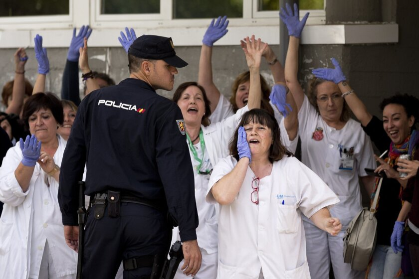 "Medical practitioners shout against Spain's Prime Minister Mariano Rajoy during his visit to the Carlos III hospital in Madrid, Spain, Friday, Oct. 10, 2014. A Spanish hospital official says the nursing assistant infected with Ebola is ""stable,"" hours after authorities described her condition as critical. She is the first person known to have caught the disease outside the outbreak zone in West Africa. She contracted the virus while helping treat a Spanish missionary who became infected in West Africa, and later died. (AP Photo/Daniel Ochoa de Olza)"