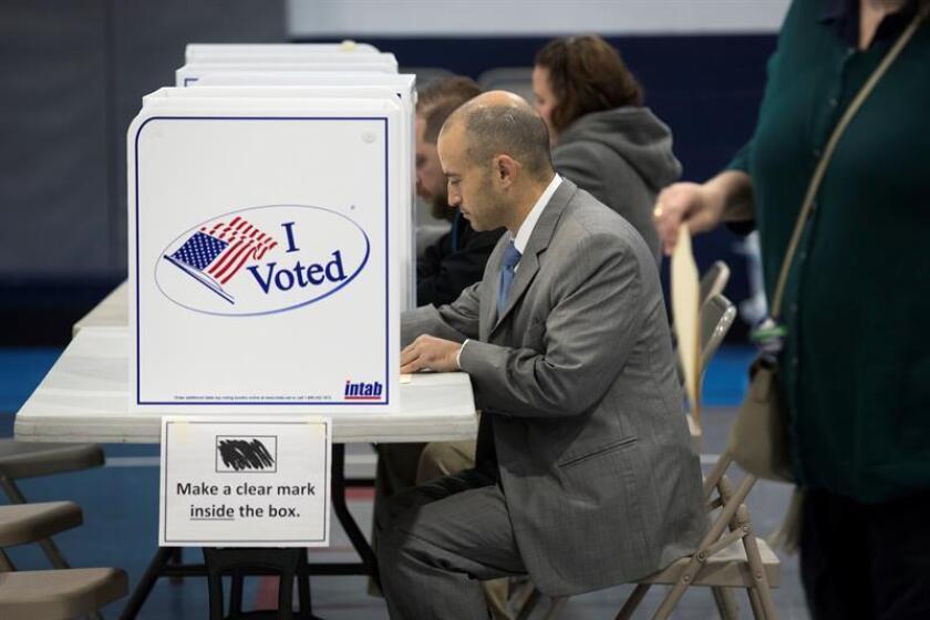 Fotografía donde se observa a varios votantes que rellenan sus papeletas antes de ejercer su derecho al voto en Virginia. EFE/Archivo