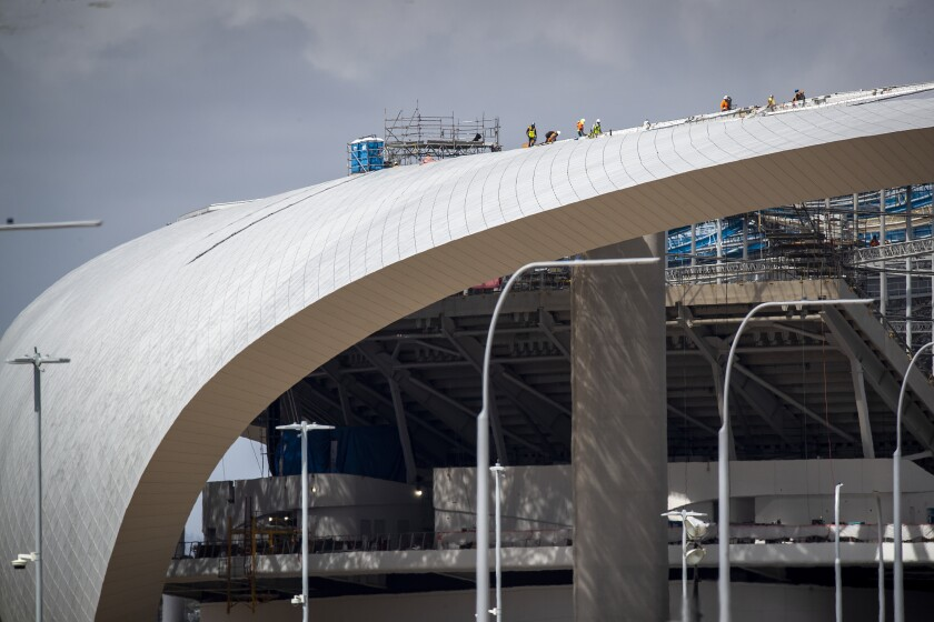 Construction workers are shown at SoFi Stadium in Inglewood on March 19, 2020.
