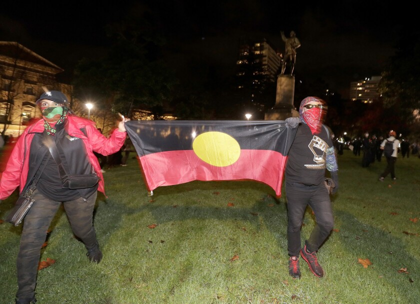 Protestors carry an Aboriginal flag as the walk past a statue of British explorer James Cook in Sydney, Friday, June 12, 2020, to support U.S. protests over the death of George Floyd. Hundreds of police disrupted plans for a Black Lives Matter rally but protest organizers have vowed that other rallies will continue around Australia over the weekend despite warnings of the pandemic risk. (AP Photo/Rick Rycroft)