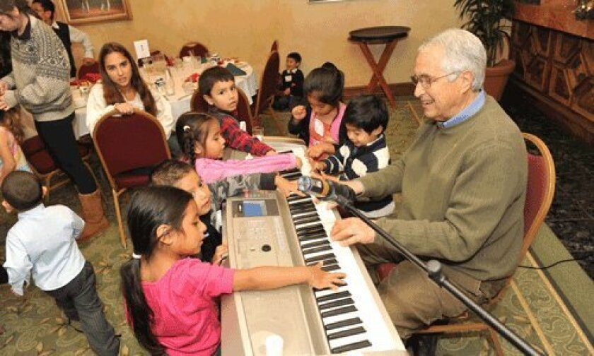Dr. Ed Siegel plays the piano with the children