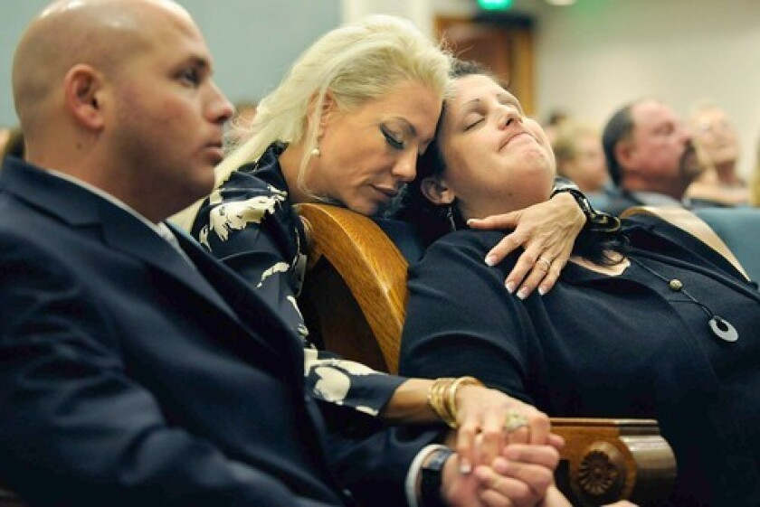 Barrie Winston, right, daughter of train crash victim Howard Pompel, is consoled by family friend Aviva Millan at a memorial service Wednesday at the Simi Valley Cultural Arts Center. Pompel's son Cliff is at left.