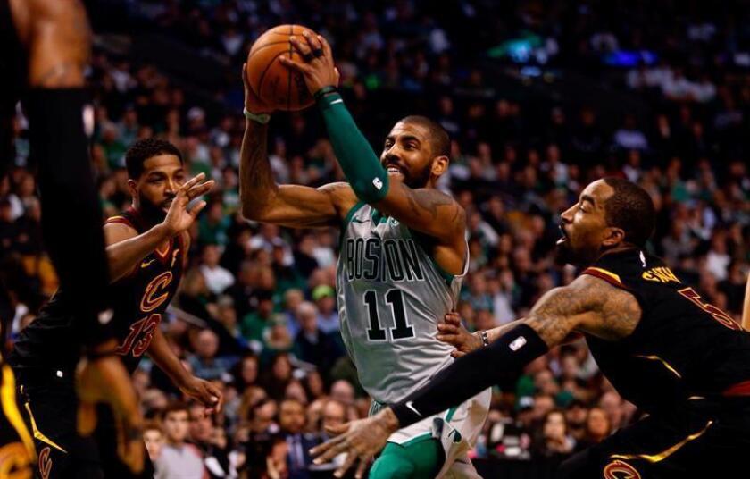En la imagen un registro del base estrella de los Celtics de Boston, Kyrie Irving (c), quien será operado el próximo sábado de la rodilla izquierda y se perderá lo que resta de temporada de la NBA. EFE/Archivo